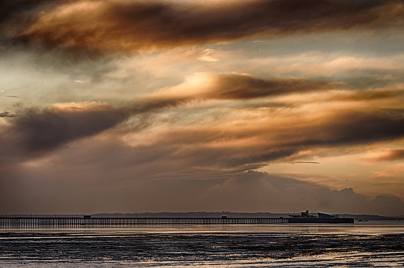 Shot at sunrise, with the clouds blocking the rising sun over Southend pier with the tide out